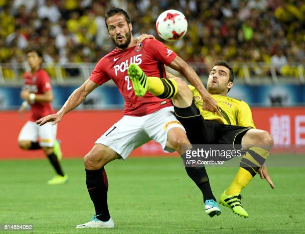 Dortmund defender Sokratis Papastathopoulos fights for the ball with Urawa Reds forward Zlatan during their friendly football match between Japan's...