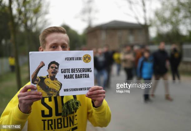 Dortmund fan displays a message for Marc Bartra who was injured in the attack on the team coach prior to the UEFA Champions League Quarter Final...