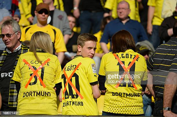 Dortmund fan wear the shirt of Dortmund's midfielder Mario Goetze with an X though it as he is transfering to Bayern Munich prior to the German first...