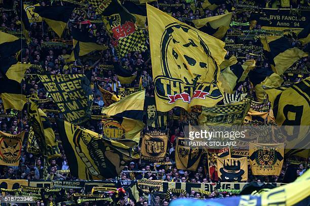 Dortmund fans hold up scarves and flags prior to the German Bundesliga first division football match between Borussia Dortmund and Werder Bremen in...