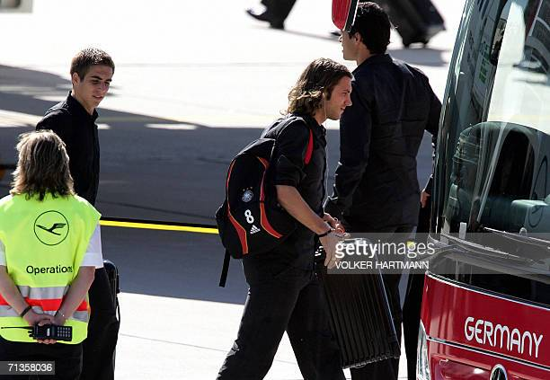 Germany's Torsten Frings walks across the tarmac past German midfielder Michael Ballack and followed by German defender Philipp Lahm to a waiting bus...