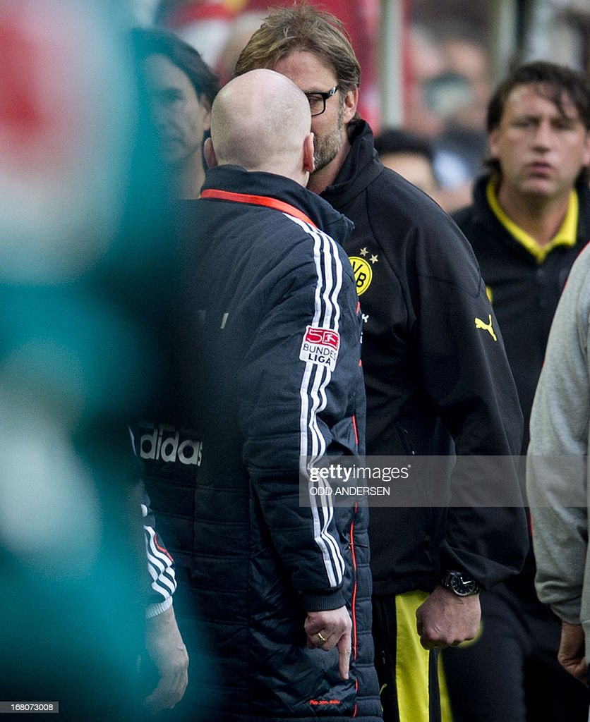 Dortmund head coach Juergen Klopp (R) faces off with Bayern Munich's sports director Matthias Sammer (L) ensuing an argument on the pitch that saw Bayern player Rafinha (not in picture) sent off for a second yellow card during the German first division Bundesliga football match BVB Borussia Dortmund vs FC Bayern Munich in Dortmund, western Germany on May 4, 2013. The match ended in a 1-1 draw. AFP PHOTO / ODD ANDERSEN ALTERNATIVE CROP
