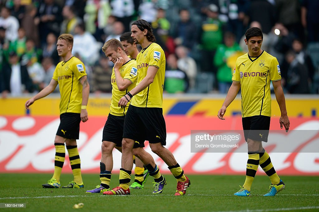 Dortmund players look dejected after being defeated in the Bundesliga match between Borussia Moenchengladbach and Borussia Dortmund at Borussia-Park on October 5, 2013 in Moenchengladbach, Germany.