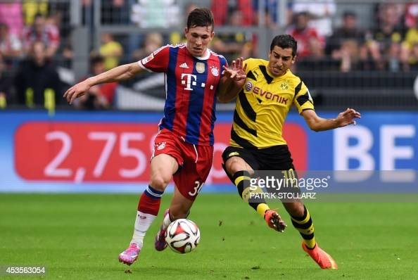Dortmund's Armenian midfielder Henrikh Mkhitaryan and Bayern Munich's defender Pierre Emile Hojbjerg vie during the German Supercup football match...