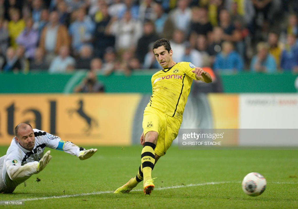 Dortmund's Armenian midfielder Henrikh Mkhitaryan scores the second goal past 1860 Munich's Hungarian goalkeeper Gabor Kiraly (L) during the second round football match of the German Cup (DFB - Pokal) TSV 1860 Munich vs Borussia Dortmund on September 24, 2013 in Munich, southern Germany. DURING THE MATCH AND PROHIBITS MOBILE (MMS) USE