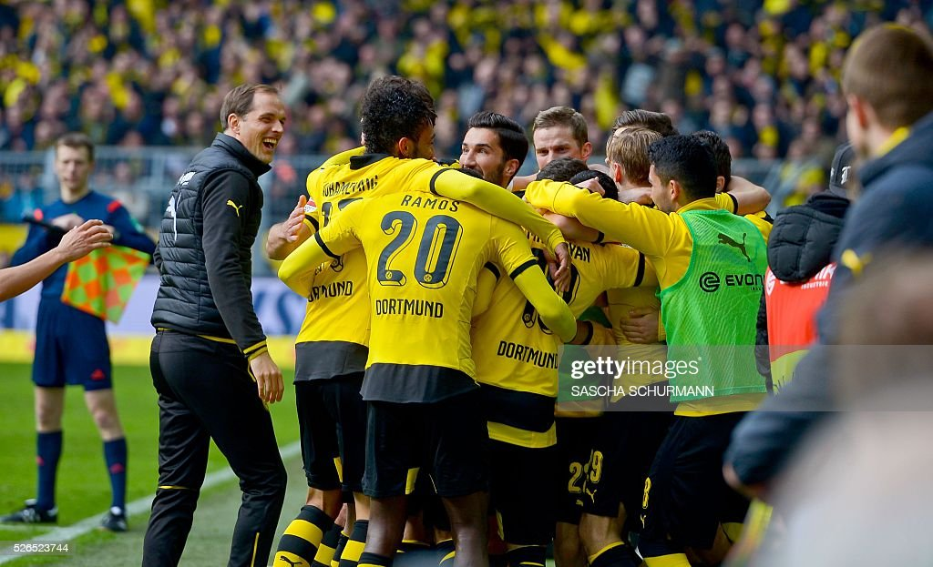 Dortmunds Aubameyang Dortmund's Gabonese striker Pierre-Emerick Aubameyang (2nd L) celebrates scoring the 5-0 goal with his team-mates and coach Thomas Tuchel (L) during the German first division Bundesliga football match Borussia Dortmund vs VfL Wolfsburg, in Dortmund, western Germany, on April 30, 2016. / AFP / Sascha SCH��RMANN
