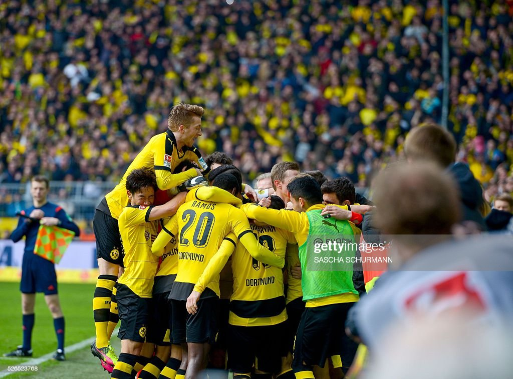 Dortmunds Aubameyang Dortmund's Gabonese striker Pierre-Emerick Aubameyang (hidden) celebrates scoring the 5-0 goal with his team-mates during the German first division Bundesliga football match Borussia Dortmund vs VfL Wolfsburg, in Dortmund, western Germany, on April 30, 2016. / AFP / Sascha SCH��RMANN