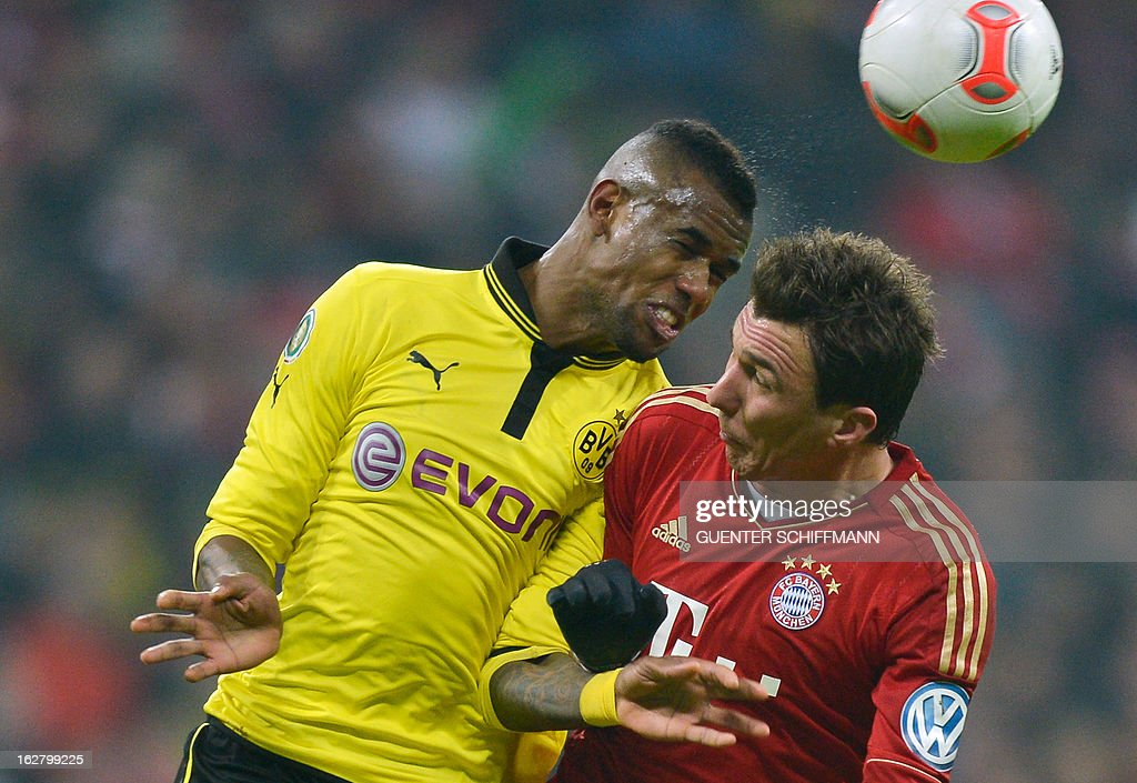 Dortmund's Brazilian defender Felipe Santana and Bayern Munich's Croation striker Mario Mandzukic (R) vie for the ball during the German Cup quarter-final football match FC Bayern Munich vs Borussia Dortmund in Munich, southern Germany, on February 27, 2013. AFP PHOTO / GUENTER SCHIFFMANN DURING THE MATCH AND PROHIBITS MOBILE (MMS) USE