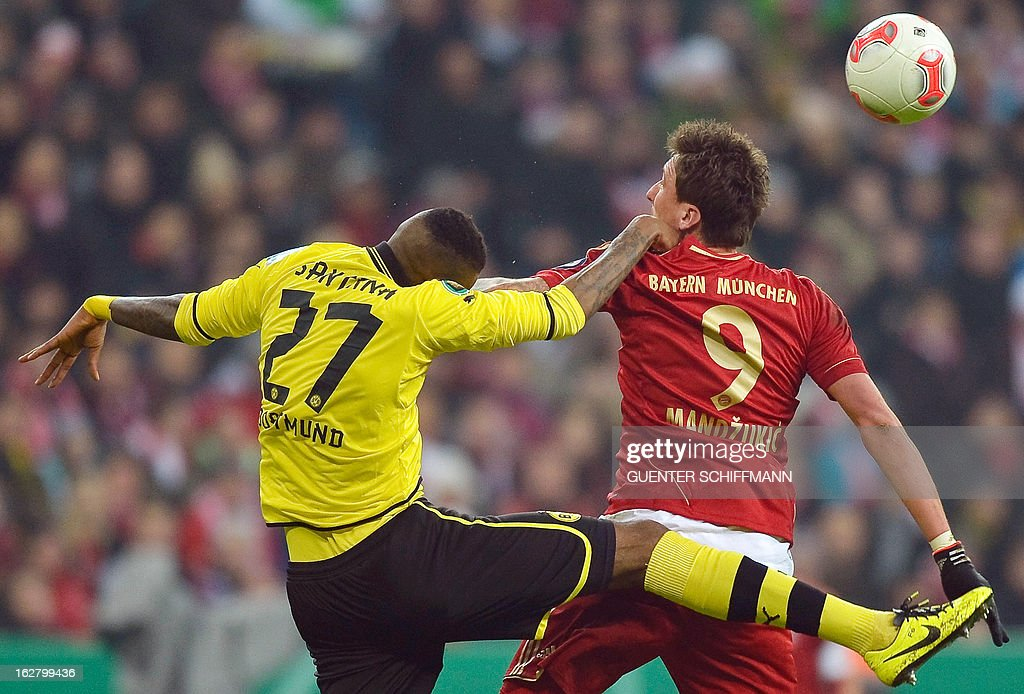 Dortmund's Brazilian defender Felipe Santana (L) and Bayern Munich's Croation striker Mario Mandzukic vie for the ball during the German Cup quarter-final football match FC Bayern Munich vs Borussia Dortmund in Munich, southern Germany, on February 27, 2013. AFP PHOTO / GUENTER SCHIFFMANN DURING THE MATCH AND PROHIBITS MOBILE (MMS) USE DURING AND FOR FURTHER TWO HOURS AFTER THE MATCH. FOR MORE INFORMATION CONTACT DFL.