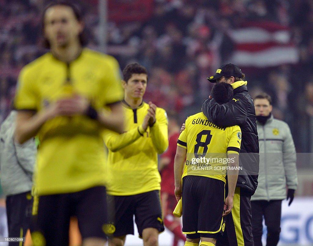Dortmund's coach Juergen Klopp hugs Dortmund's German midfielder Ilkay Guendogan after the German Cup quarter-final football match FC Bayern Munich vs Borussia Dortmund in Munich, southern Germany, on February 27, 2013. Bayern Munich won the match 1-0. AFP PHOTO / GUENTER SCHIFFMANN DURING THE MATCH AND PROHIBITS MOBILE (MMS) USE