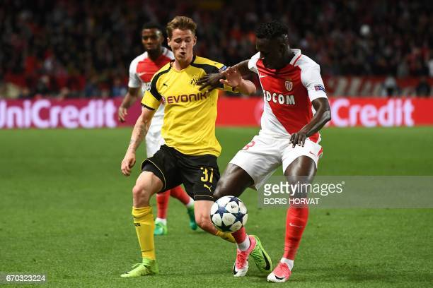Dortmund's defender Erik Durm and Monaco's French defender Benjamin Mendy vie for the ball during the UEFA Champions League 2nd leg quarterfinal...