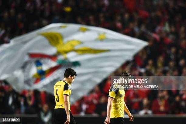Dortmund's defender Marcel Schmelzer and Dortmund's Spanish defender Marc Bartra leave the pitch at the end of the UEFA Champions League round of 16...