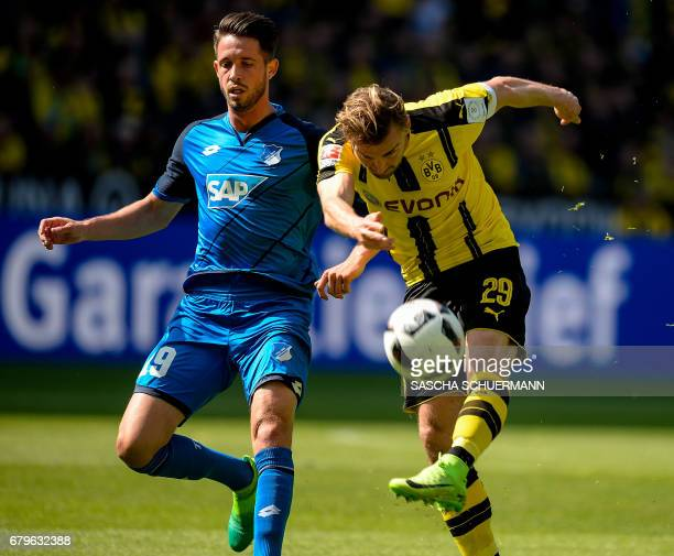 Dortmund's defender Marcel Schmelzer and Hoffenheim's forward Mark Uth vie for the ball during the German first division Bundesliga football match...