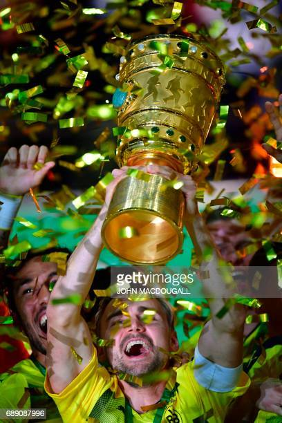 Dortmund's defender Marcel Schmelzer lifts the trophy after the German Cup final football match Eintracht Frankfurt v BVB Borussia Dortmund at the...