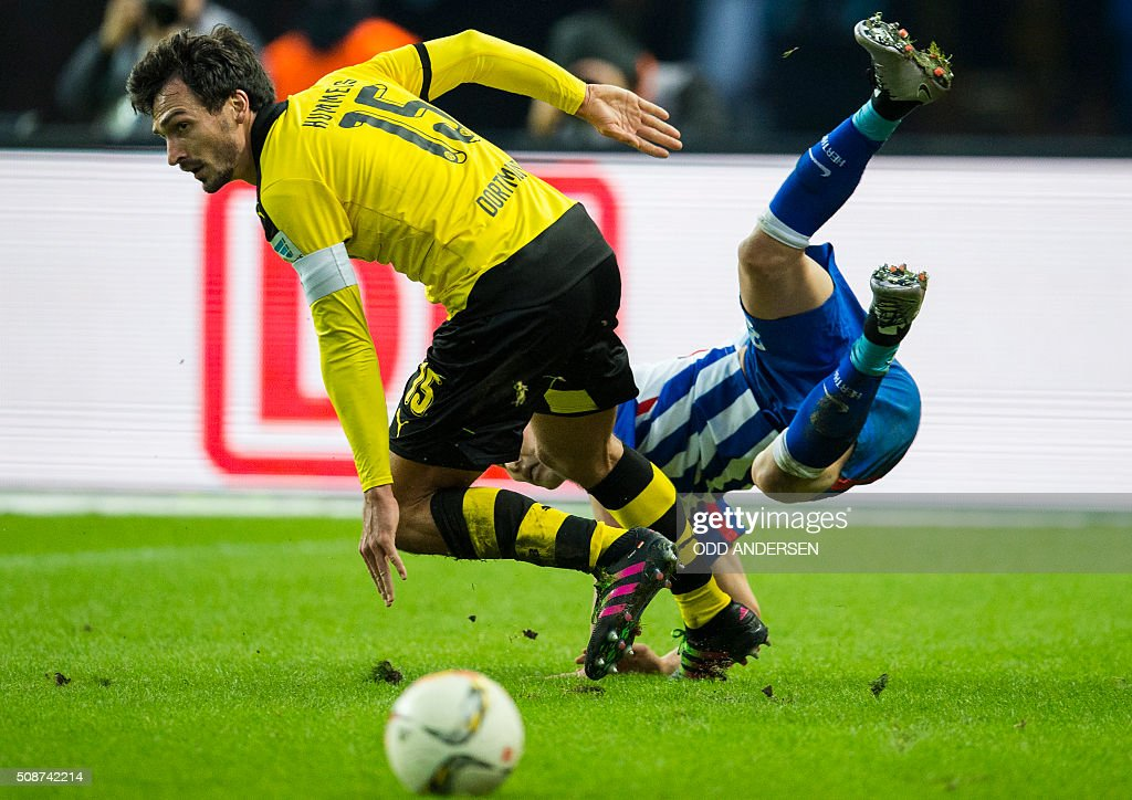 Dortmund's defender Mats Hummels (L) and Hertha Berlin's Japanese midfielder Genki Haraguchi vie for the ball during the German first division Bundesliga football match, Hertha Berlin v Borussia Dortmund, at the Olympic stadium in Berlin on February 6, 2016. / AFP / ODD ANDERSEN /