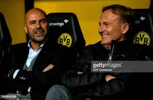 Dortmund's Dutch head coach Peter Bosz and Dortmund's CEO HansJoachim Watzke sit on the bench prior to the German first division Bundesliga football...