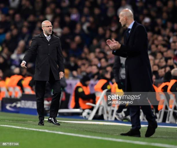 Dortmund's Dutch head coach Peter Bosz stand on the sideline beside Real Madrid's French coach Zinedine Zidane during the UEFA Champions League group...