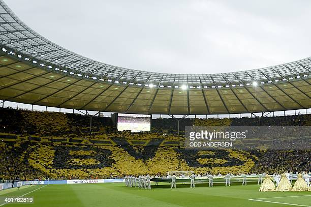 Dortmund's fans hold black and yellow posters to feature their team's logo before the start of the DFB German Cup final football match BVB Borussia...