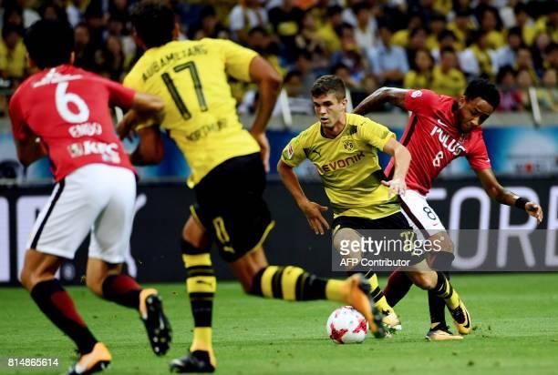 Dortmund's forward Christian Pulisic dribbles past Urawa's forward Rafael Da Silva during their friendly football match between Japan's Urawa Reds...