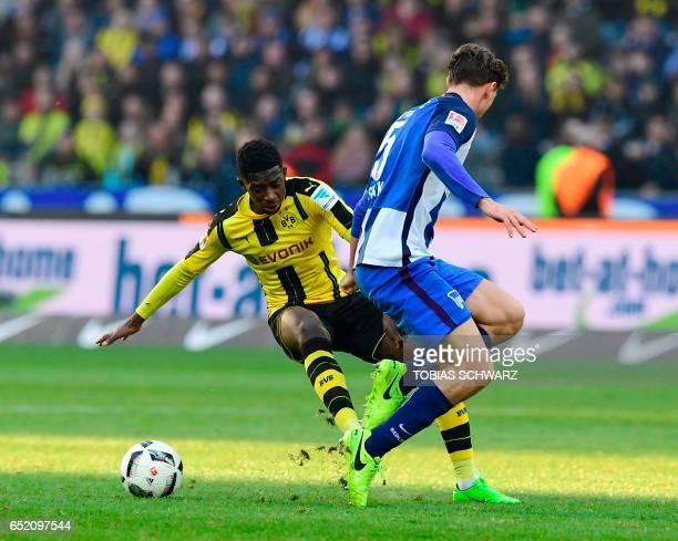 Dortmund's French midfielder Ousmane Dembele and Hertha Berlin's midfielder Niklas Stark vie for the ball during the German First division Bundesliga...