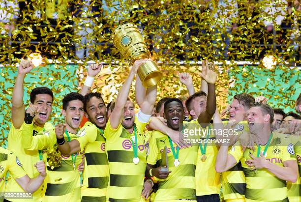 TOPSHOT Dortmund's French midfielder Ousmane Dembele and teammates celebrate with the trophy after winning the German Cup final football match...