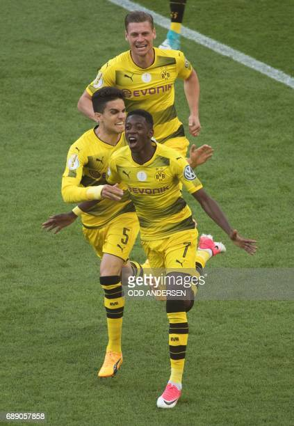 Dortmund's French midfielder Ousmane Dembele celebrates scoring the opening goal with his teammates Spanish defender Marc Bartra and Polish defender...