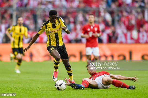 Dortmund's French striker Ousmane Dembele and Bayern Munich's Spanish midfielder Xabi Alonso vie for the ball during the German first division...