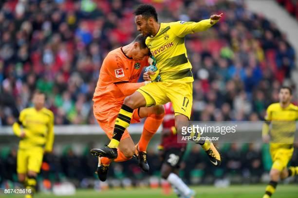 Dortmund's Gabonese forward PierreEmerick Aubameyang and Hanover's German goalkeeper Philipp Tschauner vie for the ball during the German First...