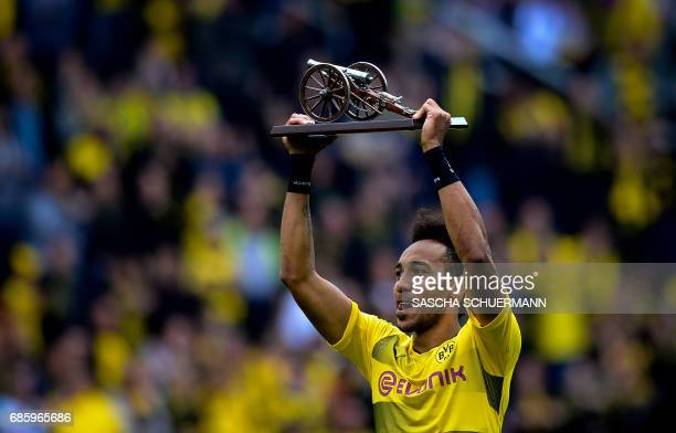 TOPSHOT Dortmund's Gabonese forward PierreEmerick Aubameyang lifts the trophy as the Bundesliga's topscorer after the German first division football...