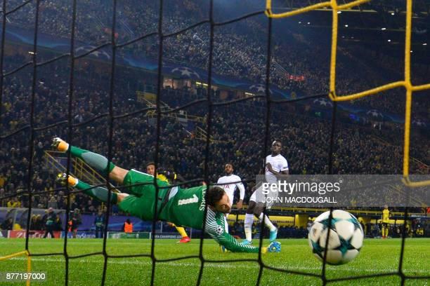 TOPSHOT Dortmund's Gabonese forward PierreEmerick Aubameyang scores the opening goalpast Tottenham Hotspur's French goalkeeper Hugo Lloris during the...