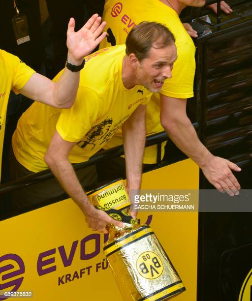 Dortmund's head coach Thomas Tuchel hands over a mockup of the trophy to fans as he and his players arrive at Borsigplatz during celebrations after...