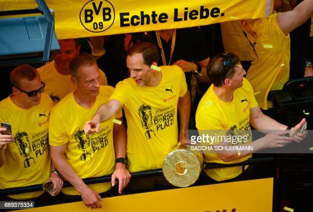 Dortmund's head coach Thomas Tuchel holds a mockup of the trophy as he and his players arrive at Borsigplatz during celebrations after winning the...
