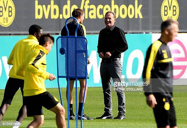 Dortmund's head coach Thomas Tuchel talks to Dortmund's CEO HansJoachim Watzke during a training session in Dortmund on September 26 2016 on the eve...