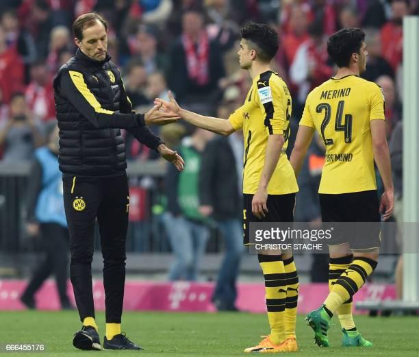 Dortmund's head coach Thomas Tuchel thanks Dortmund's Spanish defender Marc Bartra and Dortmund's Spanish midfielder Mikel Merino after the German...
