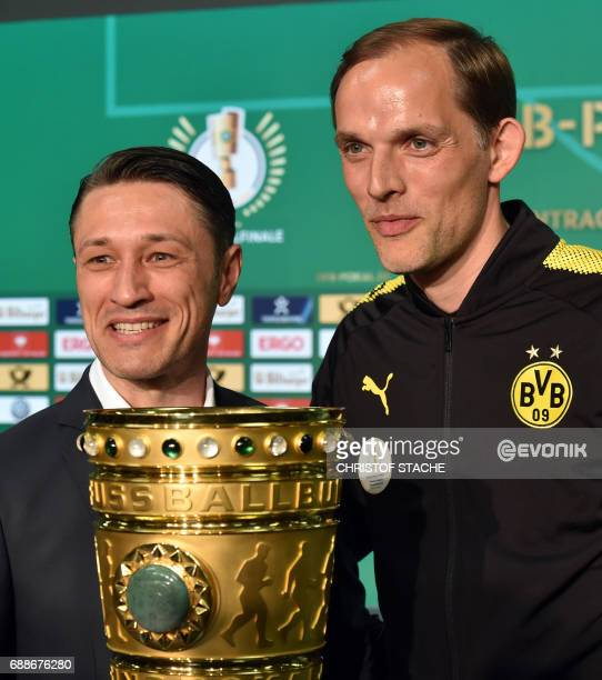 Dortmund's headcoach Thomas Tuchel and Frankfurt's Croatian headcoach Niko Kovac laugh behind the trophy after a press conference on the eve of the...
