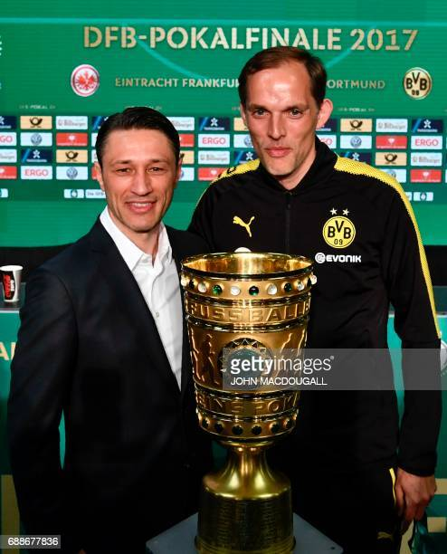 Dortmund's headcoach Thomas Tuchel and Frankfurt's Croatian headcoach Niko Kovac pose for photographers behind the trophy after a press conference on...