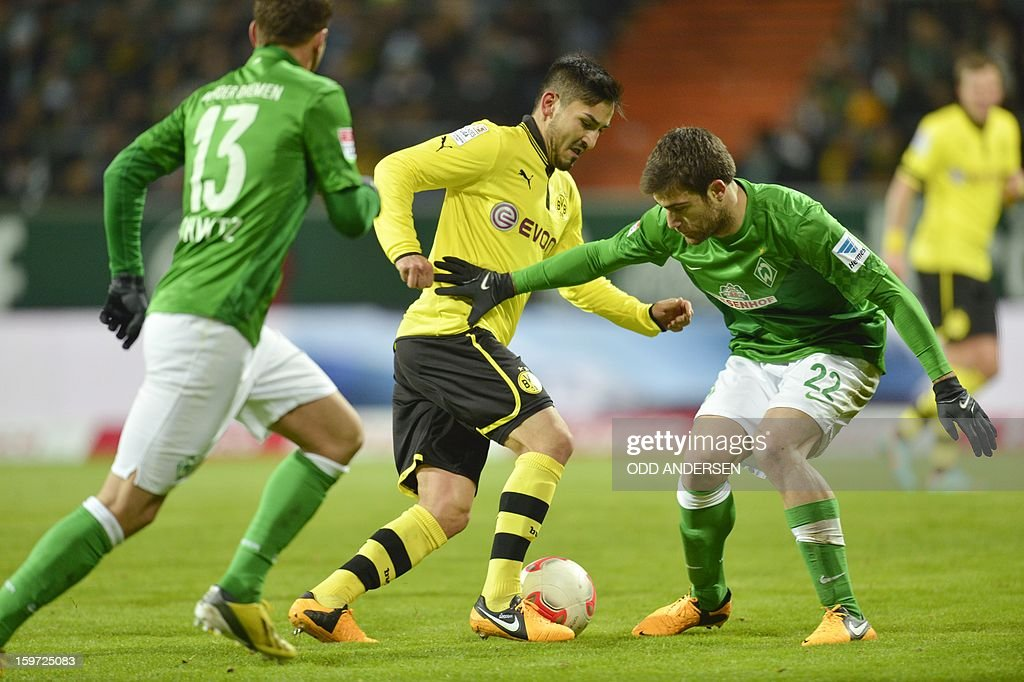 Dortmund's Ilkay Guendogan (C) vies for the ball with Bremen's Sokratis Papastathopoulos of Greece (R) and Bremen's Lukas Schmitz during the German first division Bundesliga football match Werder Bremen vs Borussia Dortmund at the Weser stadium in Bremen on January 19, 2013.