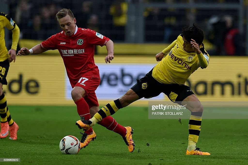 Dortmund's Japanese midfielder Shinji Kagawa (R) and Hanover's Danish striker Uffe Manich Bech vie for the ball during the German first division Bundesliga football match of Borussia Dortmund vs Hannover 96 in Dortmund, western Germany, on February 13, 2016. / AFP / PATRIK STOLLARZ /