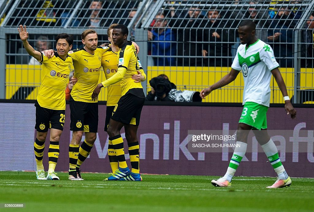 Dortmund's Japanese midfielder Shinji Kagawa (L) celebrates scoring the 1-0 goal with his team-mates during the German first division Bundesliga football match Borussia Dortmund vs VfL Wolfsburg, in Dortmund, western Germany, on April 30, 2016. / AFP / Sascha SCH��RMANN