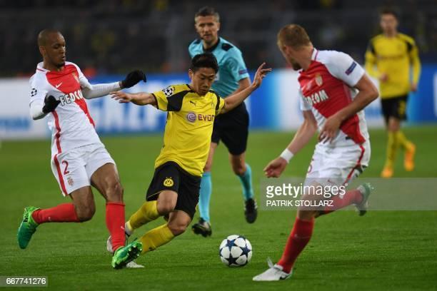 Dortmund's Japanese midfielder Shinji Kagawa is pressured Monaco's Brazilian defender Fabinho and Monaco's Polish defender Kamil Glik during the UEFA...