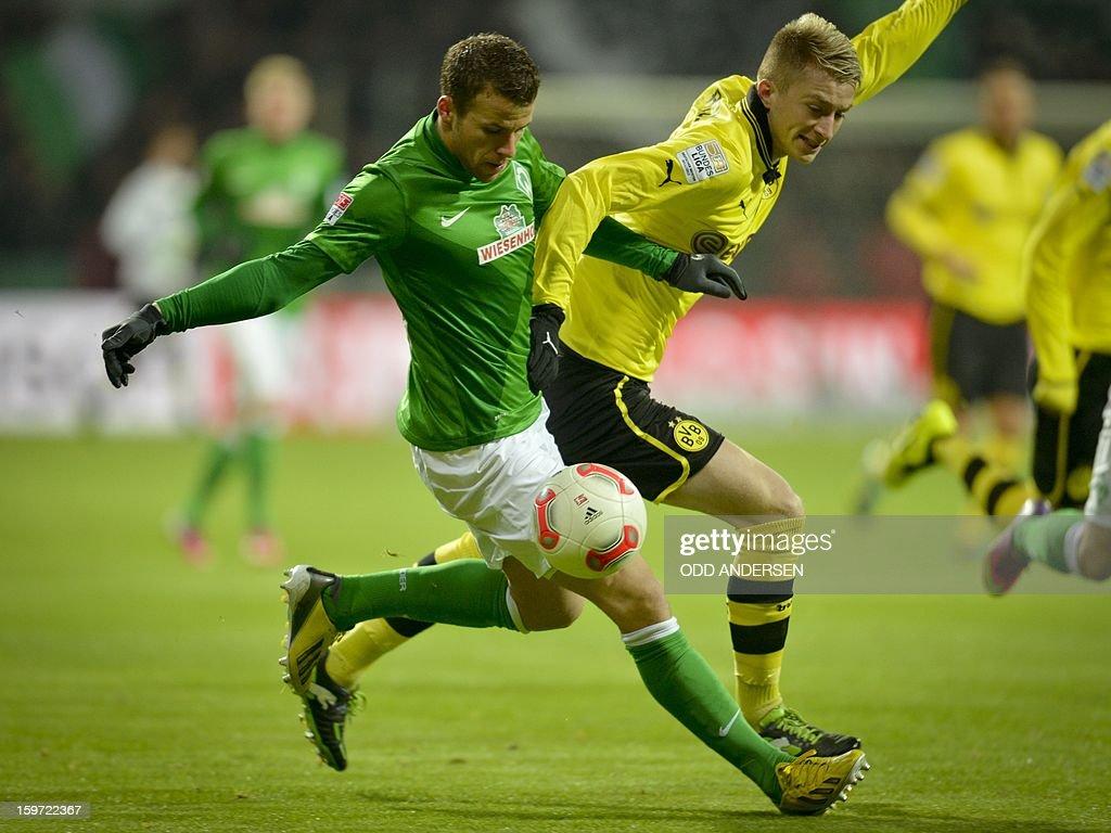 Dortmund's Marco Reus (R) and Bremen's Lukas Schmitz vie for the ball during the German first division Bundesliga football match Werder Bremen vs Borussia Dortmund at the Weser stadium in Bremen on January 19, 2013.