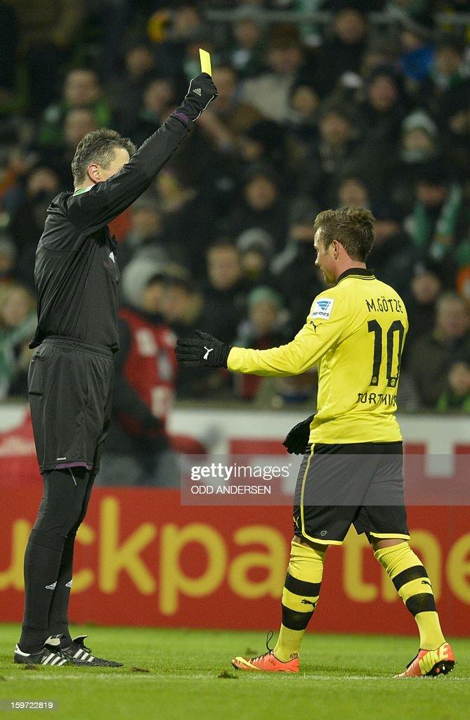 Dortmund's Mario Goetze (R) recieves a yellow card during the German first division Bundesliga football match Werder Bremen vs Borussia Dortmund at the Weser stadium in Bremen on January 19, 2013.