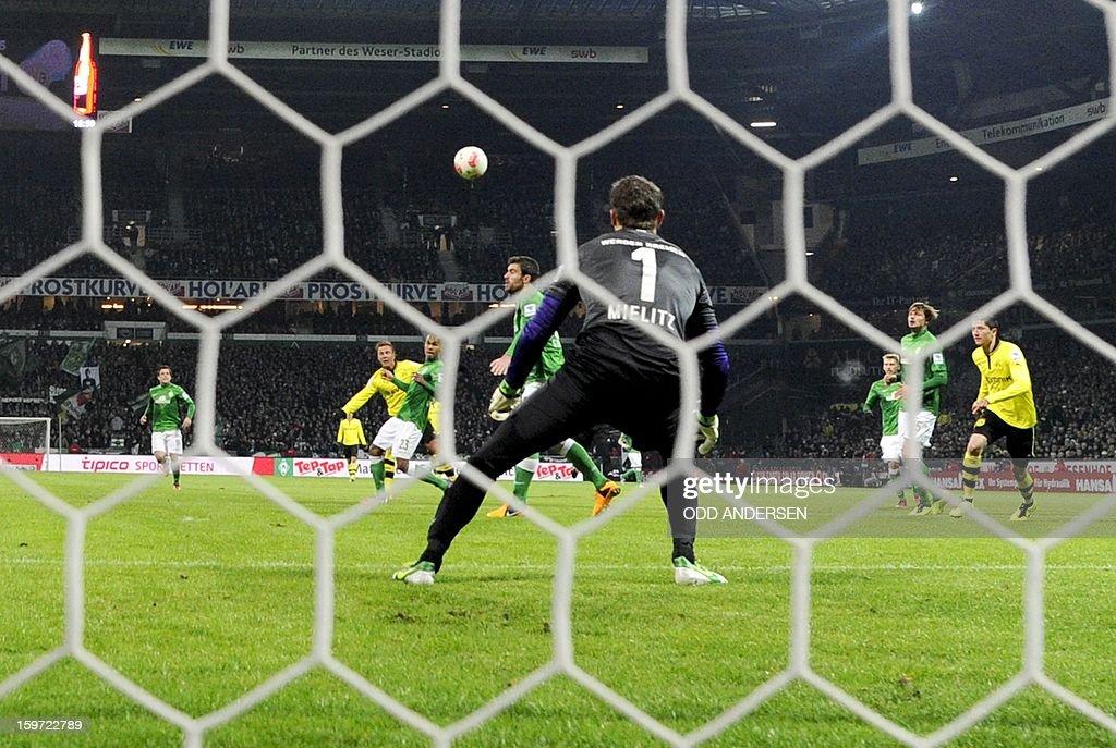Dortmund's Mario Goetze (L, yellow shirt) scores past Bremen goalkeeper Sebastian Mielitz during the German first division Bundesliga football match Werder Bremen vs Borussia Dortmund at the Weser stadium in Bremen on January 19, 2013.