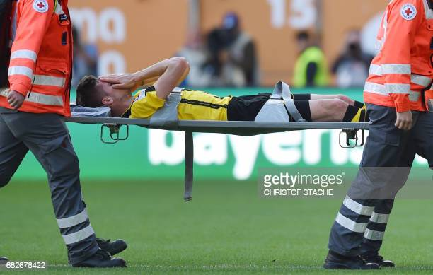 Dortmund's midfielder Julian Weigl is stretchered off the pitch during the German first division Bundesliga football match between FC Augsburg and...