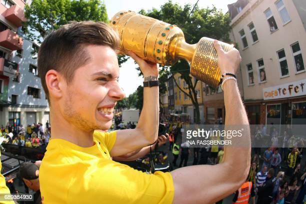 Dortmund's midfielder Julian Weigl raises the trophy as they arrive at Borsigplatz during celebrations after winning the German Cup final in Dortmund...