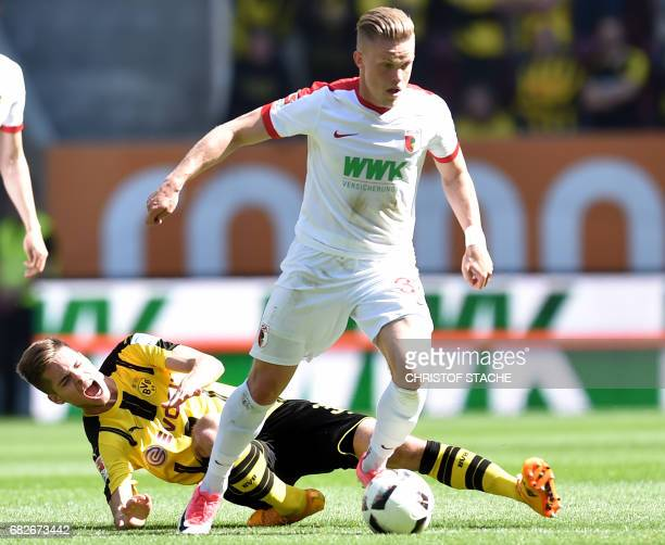 Dortmund's midfielder Julian Weigl suffers an injury as he vies for the ball with Augsburg's defender Philipp Max during the German first division...