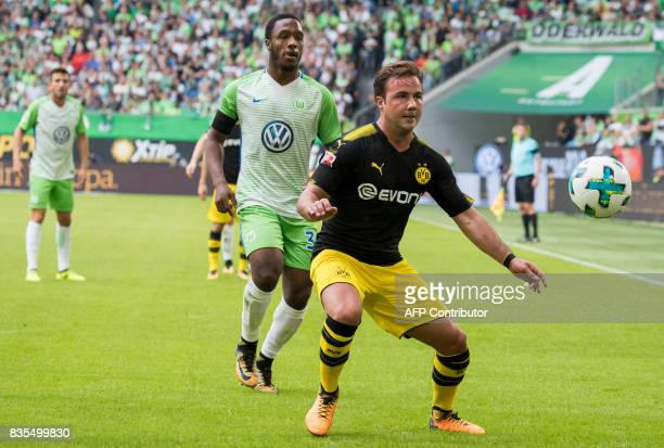 Dortmund's midfielder Mario Goetze and Wolfsburg's English forward Kaylen Hinds vie for the ball during the German First division Bundesliga football...