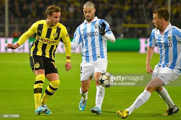 Dortmund's midfielder Mario Goetze Malaga's midfielder Isco and Malaga's midfielder Ignacio Camacho vie for the ball during the UEFA Champions League...