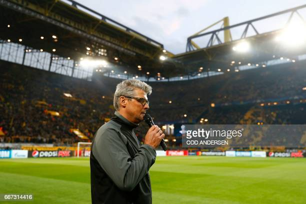 Dortmund's Norbert Dickel announces the postponed of the match after the team bus of Borussia Dortmund had some windows broken by an explosion some...