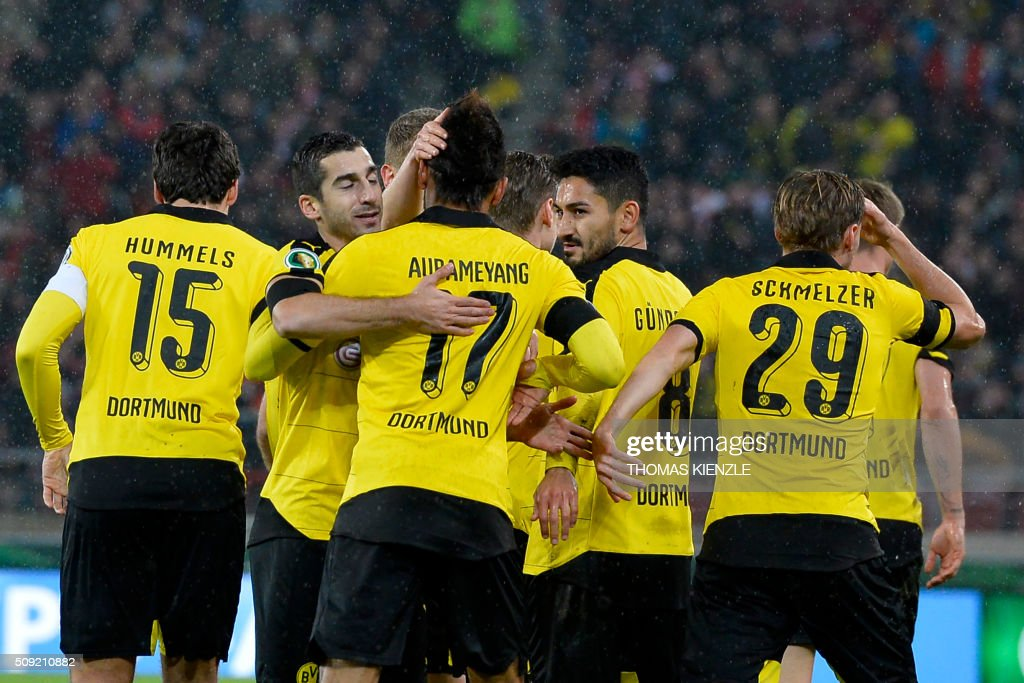 Dortmund's players celebrate after they scored the opening goal during the German Cup ( Pokal ) quarter final football match VfB Stuttgart v Borussia Dortmund on February 9, 2016 in Stuttgart. / AFP / Thomas Kienzle / AT +49 69 67880 /